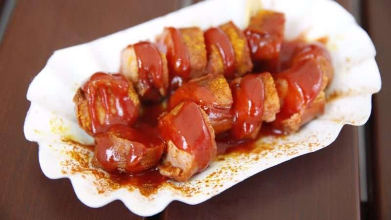 A paper plate covered in currywurst