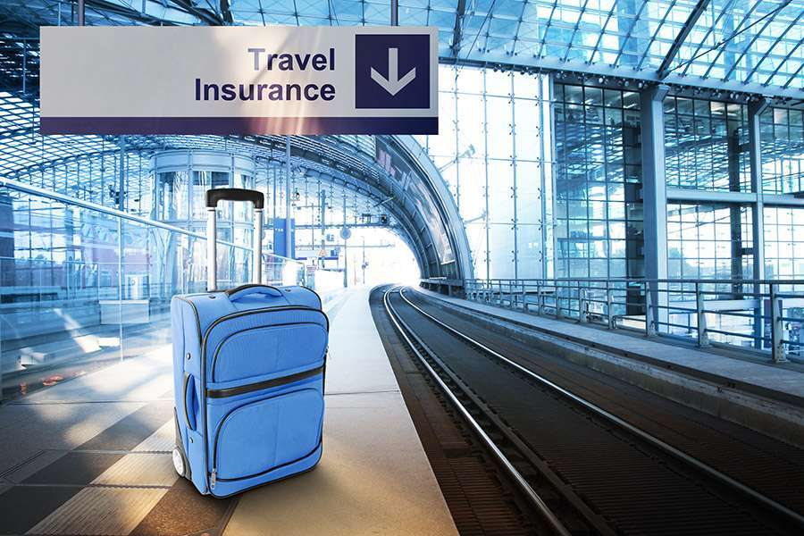 Luggage at airport under travel insurance sign
